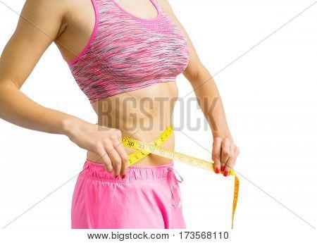 Woman measuring waist with measure tape around it
