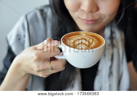 Smiling Female Holding Coffee With Latte Art