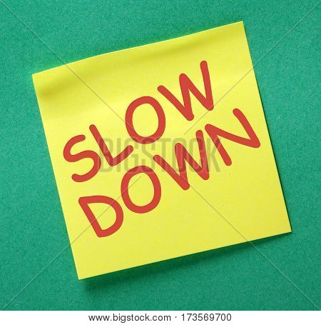The words Slow Down in red text on a yellow sticky note as a reminder to take time out and avoid stress