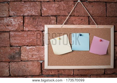 paper note on wood board and brick background
