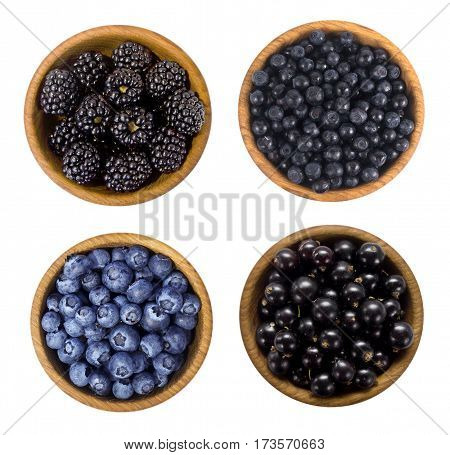 Black and blue berries. Blackberries blueberries currants and blueberries in a wooden bowls isolated on white background. Top view. Berries closeup.
