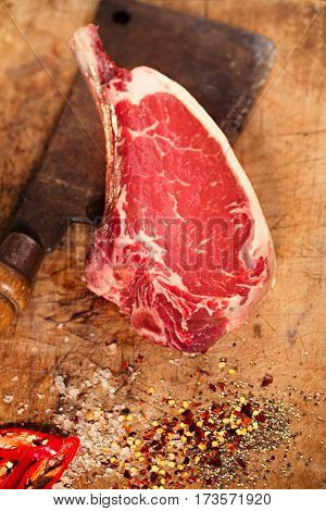 raw beef meat steak on wooden table with meat cleaver and spices