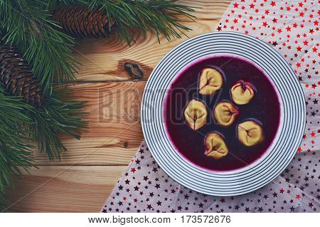 Polish red borscht with dumplings on a wooden table