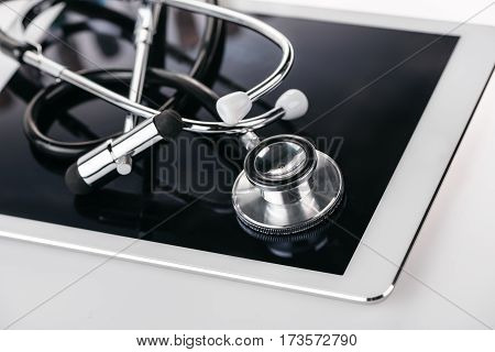 close up view of reflex hammer and stethoscope on digital tablet on white
