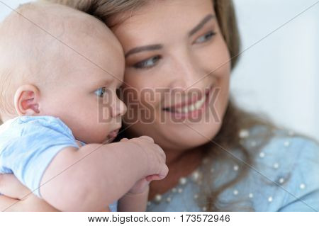 Portrait of a young woman holding baby boy