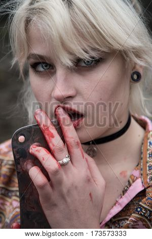 Russian young girl with blue eyes and blond hair with a bloody butcher knife in her hand. She is dressed in Chinese clothes and she is having a fashion shoot in the forest with dark aesthetics.