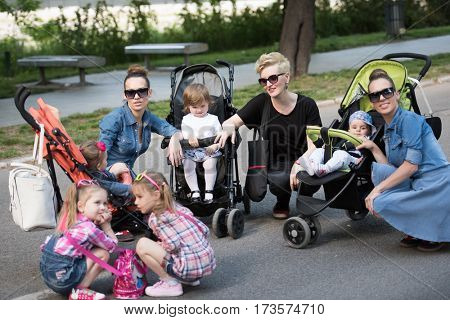 portrait of a group of young beautiful mother with children on a sunny day in the park