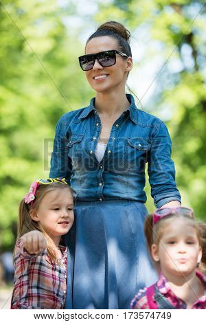 young beautiful mother enjoying with her daughters on a sunny day in the park