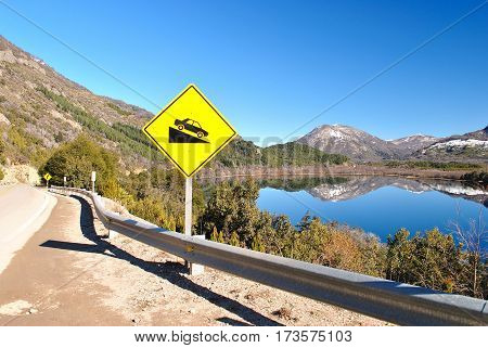 Patagonian road beside a lake, with a mountain in the background and a yellow sign in the front