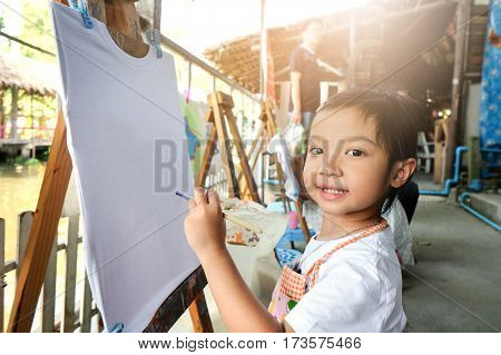 Asian child girl are using paint brushes on a white T-shirt.