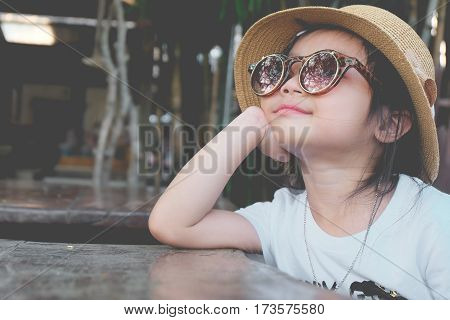 Asian child girl wearing hat Pose hands chin