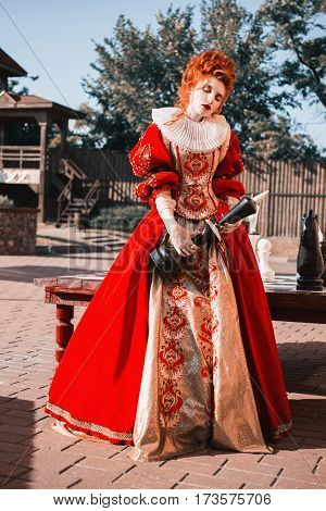 Historical fashion style. Photo in fashion style. Fashion concept. Princess fashion dress.The Red Queen is playing chess. Red-haired woman in a chic vintage dress. Fashion Photo