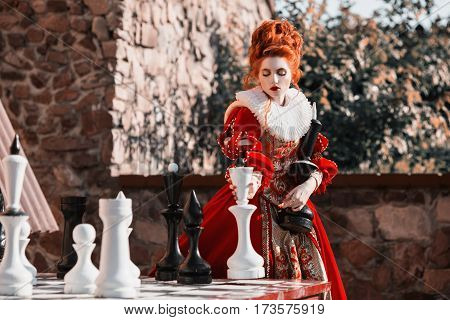 The Red Queen is playing chess. Red-haired woman in a chic vintage dress. Fashion Photo of queen play chess. Fashion style. Stylish queen