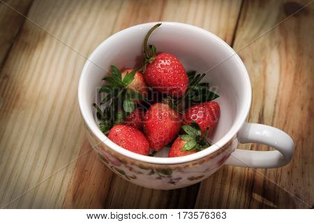Strawberry fresh berries in white coffee cup on a wooden table.