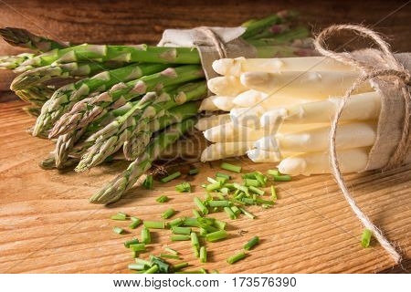 Fresh green and white asparagus with parsley on a wooden table
