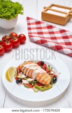 Salmon steak grilled with herbs and lemon, spicy white sauce, grilled vegetables and olives on a white plate on a light wooden background restaurant. Close-up.