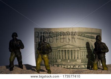 Silhouette of military soldiers on dollars background