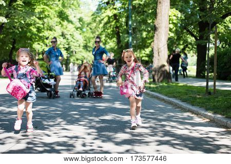 Young beautiful twins mother with children enjoying a sunny day in city park