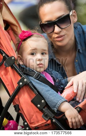 portrait of a beautiful young mother with sunglasses and a baby in a stroller on a sunny day in the park