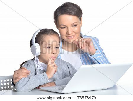 mother and daughter using laptop posing against white