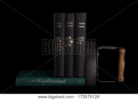 UMEA, SWEDEN ON DECEMBER 14. Stack of books written by a famous author this side a black background on December 14, 2014 in Umea, Sweden. Old iron to the right. Illustrative Editorial.