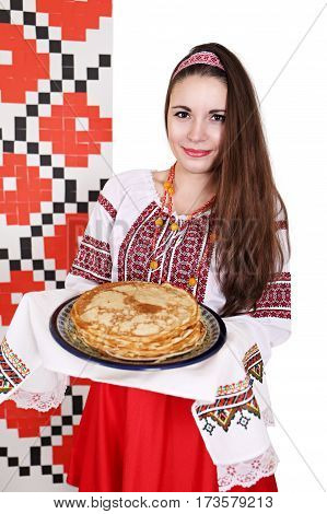 Young beautiful woman in national costume holding a plate of pancakes. Background for shrovetide