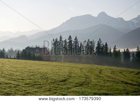 Scenic View Of A Wonderful Valley With Rural Farm House Building With Mountains On Background At Sun