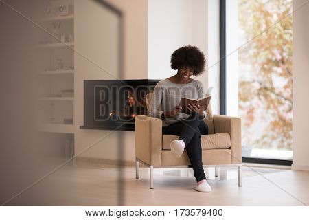 Young beautiful african american woman sitting in front of fireplace at home on a cold autumn day and reading book
