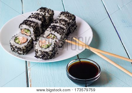 Maki Sushi with soy sauce - Roll made of Cream Cheese, Tamago, Cucumber and Smoked Eel inside. Black Tobiko outside