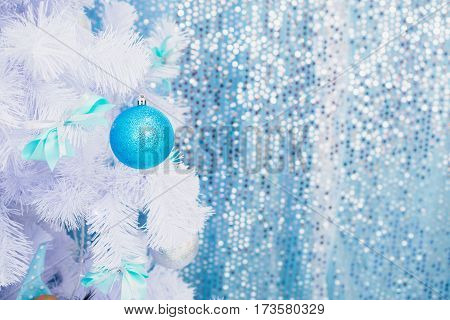Blue Christmas toy hanging on a white spruce with snow. New Year background. New Year concept. New Year blue texture