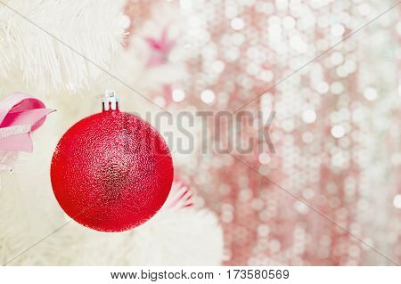 Red Christmas toy hanging on a white spruce with snow. New Year background