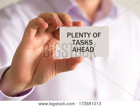 Businessman Holding A Card With Plenty Of Tasks Ahead Message