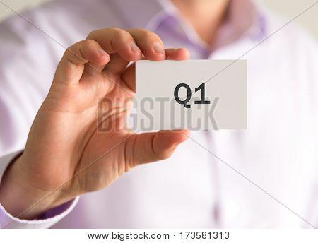 Businessman Holding A Card With Q1 Quarter 1 Message