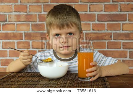 Kid with corn flakes and juice eating from wooden table