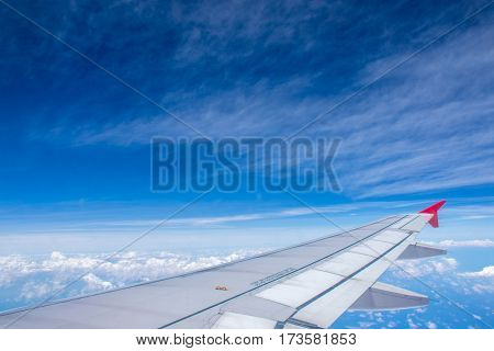 Airplane wing on beautiful blue sky with clouds