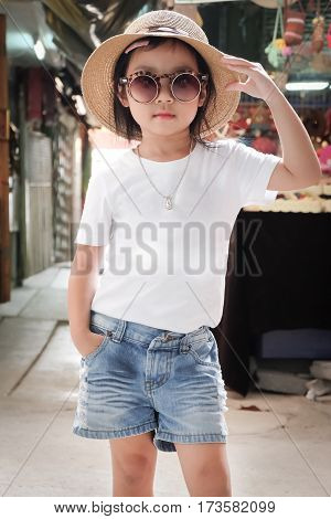 Asian girl wearing white t-shirt. Denim shorts and hats Pose Fashion