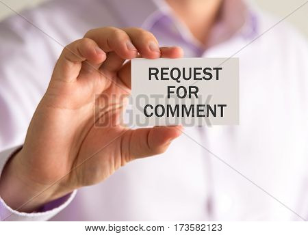 Businessman Holding A Card With Request For Comment Message