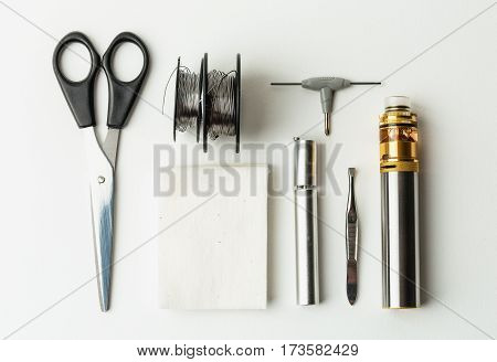 Top view of vape set tools for rebuildable atomisers, mech mod, cotton, coil Canthal, cotton, scissors, screwdriver. Set for maintenance and repair vaping devices or e-cigarettes on white background