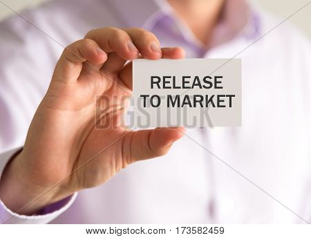 Businessman Holding A Card With Release To Market Message