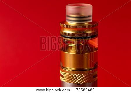 Vaping device, rebuildable atomiser with e-liquid or e-juice of glycerin on red background. Vape e-cig gadget for quit smoke. Electronic cigarette or e-cig. Copy space