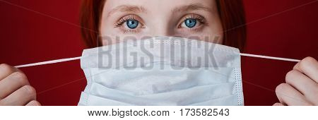 Red-haired girl doctor with a medical mask on a red background woman doctor European medical mask in hand the girl in a white turtleneck. Doctor with mask