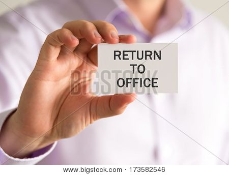 Businessman Holding A Card With Return To Office Message