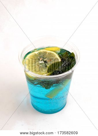 fresh mint cold cocktail with lemon and ice on a white background