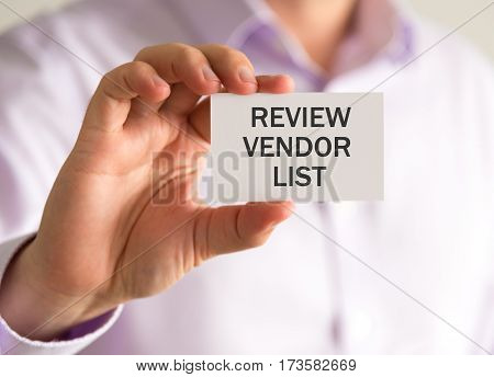 Businessman Holding A Card With Review Vendor List Message