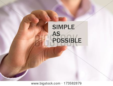 Businessman Holding A Card With Simple As Possible Message
