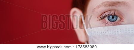 Red-haired doctor girl with a medical mask on a red background woman doctor. Woman  with intense look European half of the face hair pinned. Doctor mask concept