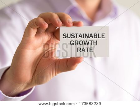 Businessman Holding A Card With Sustainable Growth Rate Message