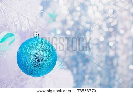 Blue Christmas toy hanging on a white spruce with snow. New Year background
