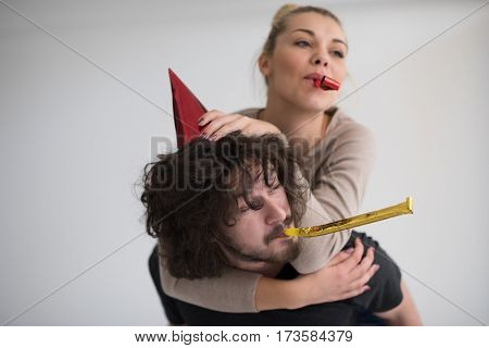 Young happy couple in party hats blowing in whistle isolated on a white background
