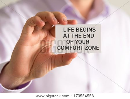 Businessman Holding A Card With Life Begins At The End Of Your Comfort Zone Message